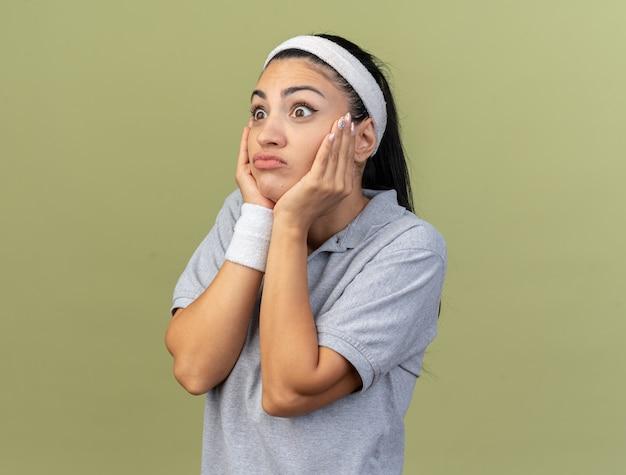 Clueless jong kaukasisch sportief meisje dat hoofdband en polsbandjes draagt die zich in profielmening bevinden die handen op gezicht houden kijkend naar kant geïsoleerd op olijfgroene muur met exemplaarruimte