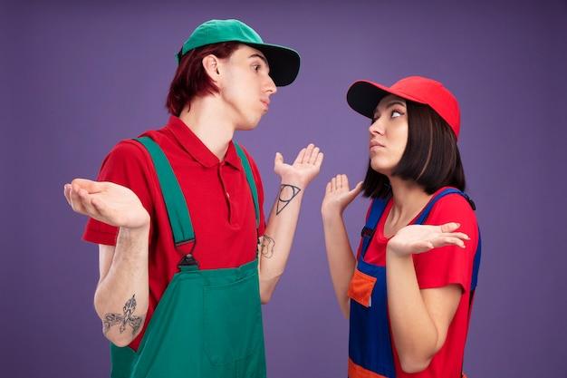 Clueless jong koppel in bouwvakker uniform en pet staande in profielweergave kijken naar elkaar doen ik weet het niet gebaar