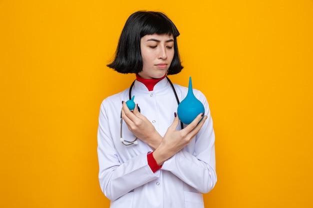Clueless jong mooi kaukasisch meisje in doktersuniform met een stethoscoop die klysma's vasthoudt en bekijkt