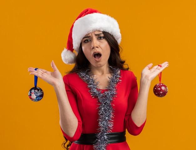 Clueless jong mooi meisje met kerstmuts en klatergoudslinger om nek met kerstballen geïsoleerd op oranje muur