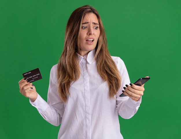 Clueless jong, vrij blank meisje houdt creditcard vast en kijkt naar telefoon geïsoleerd op groene muur met kopieerruimte