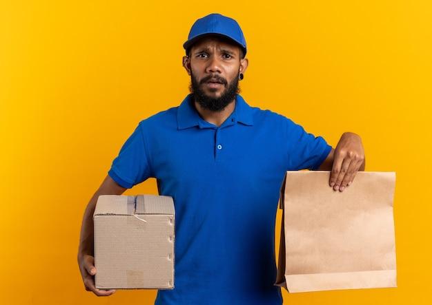 Clueless jonge afro-amerikaanse bezorger met kartonnen doos en voedselpakket geïsoleerd op een oranje achtergrond met kopieerruimte