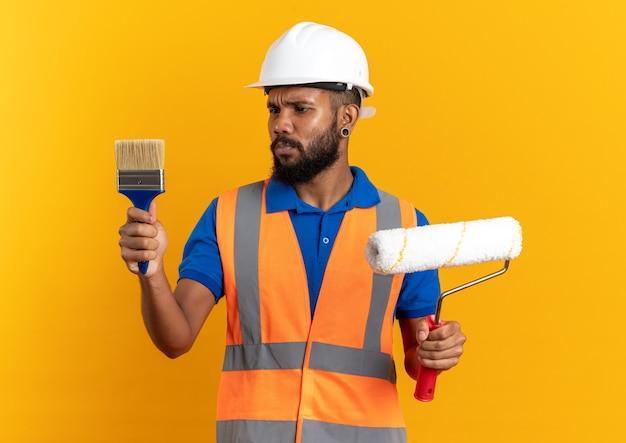 Clueless jonge afro-amerikaanse bouwer man in uniform met veiligheidshelm verfroller te houden en kijken naar kwast geïsoleerd op een oranje achtergrond met kopie ruimte