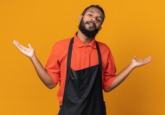 Clueless jonge afro-amerikaanse kapper draagt uniform met lege handen geïsoleerd op oranje muur