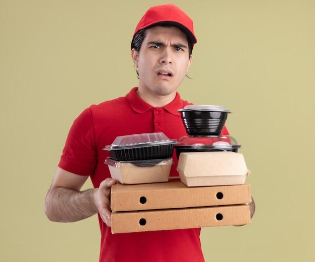 Clueless jonge bezorger in rood uniform en pet met pizzapakketten met voedselcontainers en papieren voedselpakketten erop kijkend naar voorkant geïsoleerd op olijfgroene muur