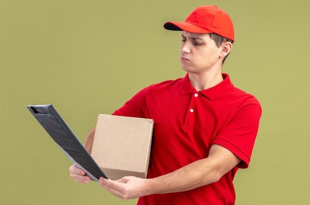 Clueless jonge blanke bezorger in rood shirt met kartonnen doos en kijken naar klembord geïsoleerd op olijfgroene muur met kopieerruimte