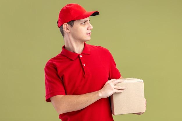 Clueless jonge blanke bezorger in rood shirt met kartonnen doos en kijkend naar kant geïsoleerd op olijfgroene muur met kopieerruimte