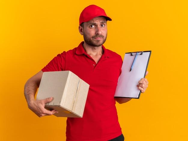 Clueless jonge blanke bezorger in rood uniform en pet met kartonnen doos en klembord