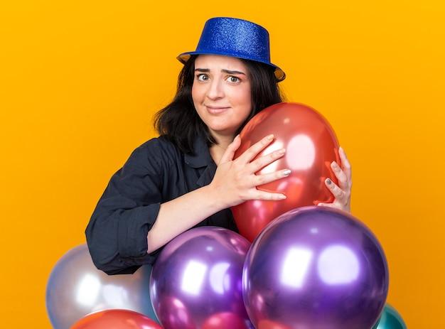 Clueless jonge blanke feestvrouw met een feestmuts die achter ballonnen staat en er een vasthoudt die naar de voorkant kijkt geïsoleerd op een oranje muur