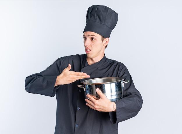 Clueless jonge blonde mannelijke kok in chef-kok uniform en pet kijkend naar de zijkant vasthouden en wijzend op pot
