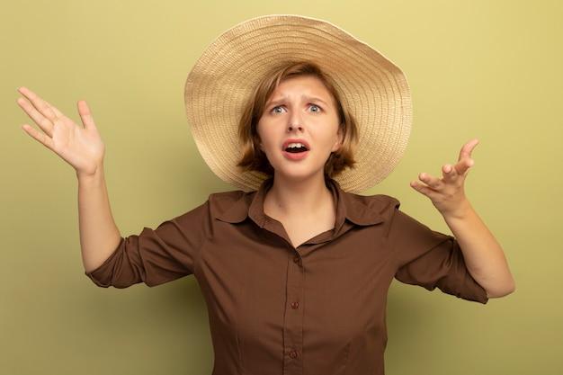 Clueless jonge blonde vrouw die strandhoed draagt die recht kijkt met lege handen