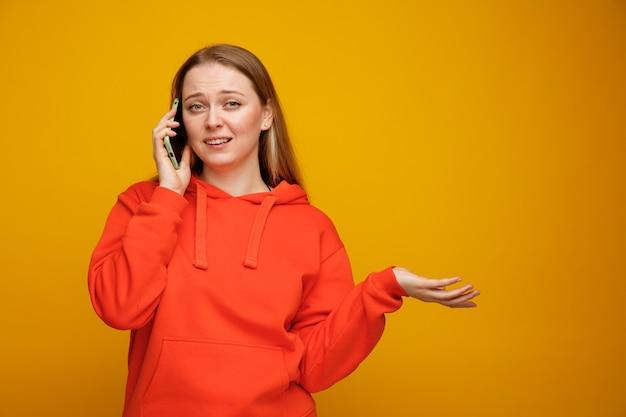 Clueless jonge blonde vrouw met lege hand praten over de telefoon