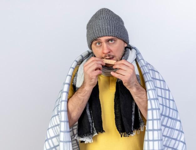 Clueless jonge blonde zieke slavische man met winter muts en sjaal gewikkeld in plaid houdt medische gips geïsoleerd op een witte muur met kopie ruimte