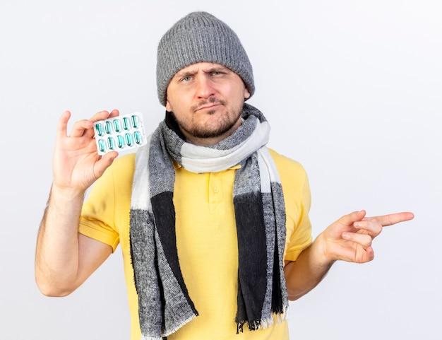 Clueless jonge blonde zieke slavische man met winter muts en sjaal houdt pakje medische pillen en punten aan kant geïsoleerd op een witte muur met kopie ruimte
