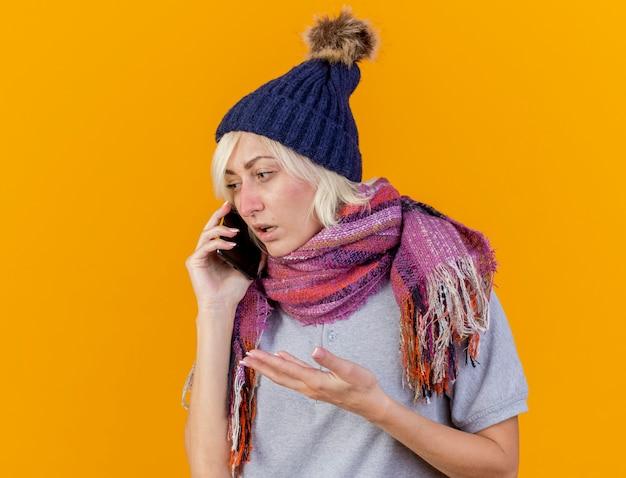 Clueless jonge blonde zieke slavische vrouw die de wintermuts en sjaal draagt, spreekt over telefoon die kant bekijkt