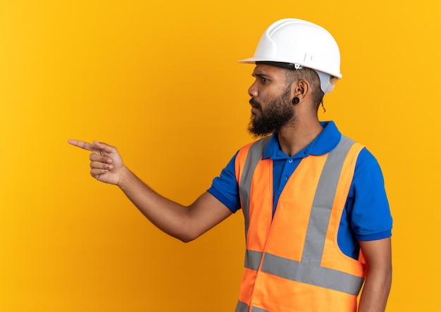 Clueless jonge bouwer man in uniform met veiligheidshelm kijkend en wijzend naar kant geïsoleerd op oranje muur met kopieerruimte