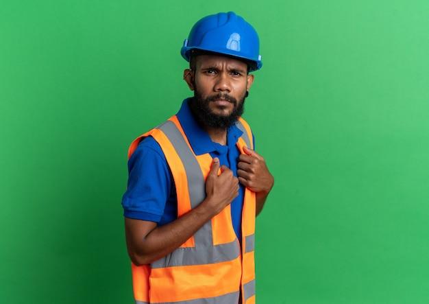 Clueless jonge bouwer man in uniform met veiligheidshelm kijkend naar voorkant geïsoleerd op groene muur met kopieerruimte