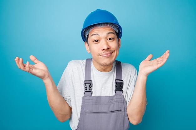 Clueless jonge bouwvakker die veiligheidshelm draagt en eenvormig doet ik weet geen gebaar