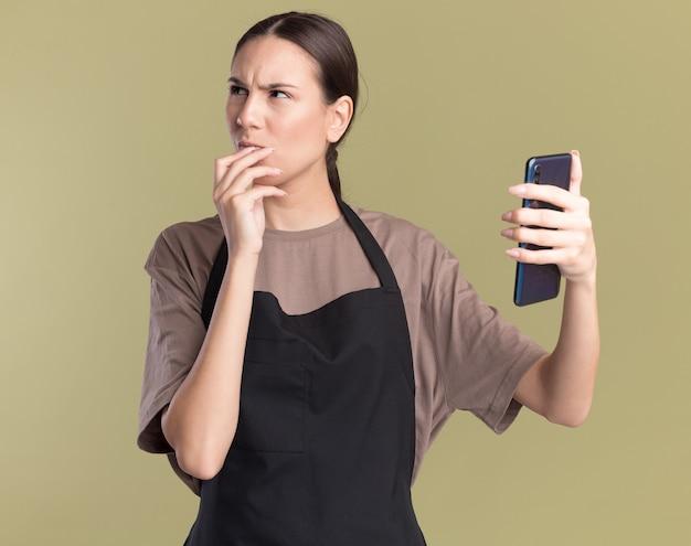 Clueless jonge brunette kapper meisje in uniform legt de hand op de kin en houdt de telefoon naar de zijkant op olijfgroen te kijken