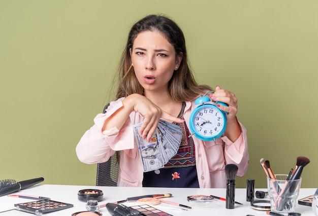 Clueless jonge brunette meisje zittend aan tafel met make-up tools die geld aanhouden en wijzend op wekker