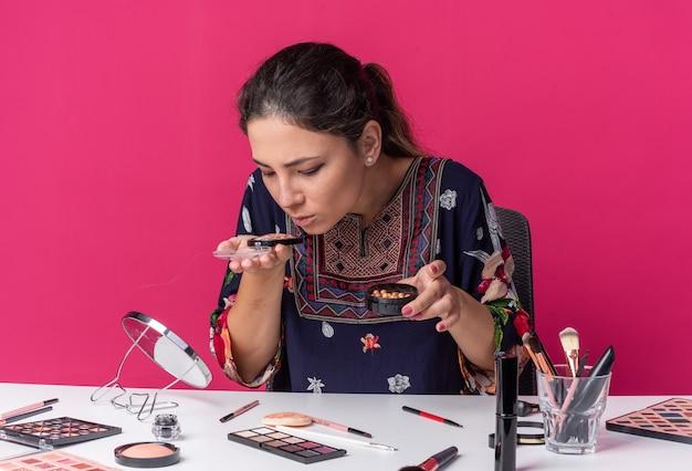 Clueless jonge brunette meisje zittend aan tafel met make-up tools houden en snuiven blos geïsoleerd op roze muur met kopie ruimte