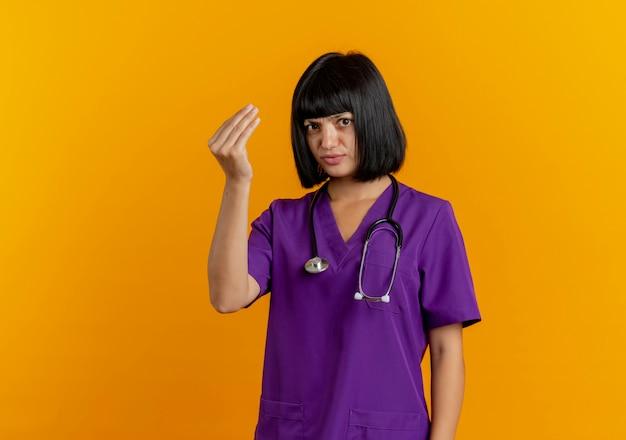 Clueless jonge brunette vrouwelijke arts in uniform met stethoscoop gebaren geld handteken geïsoleerd op een oranje achtergrond met kopie ruimte