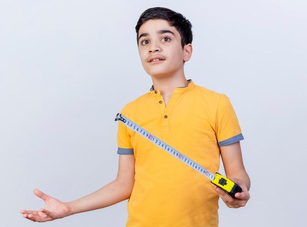 Clueless jonge kaukasische de bandmeter die van de jongensholding recht kijkt met lege die hand op witte achtergrond wordt geïsoleerd