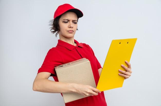 Clueless jonge mooie bezorger die kartonnen doos vasthoudt en naar klembord kijkt