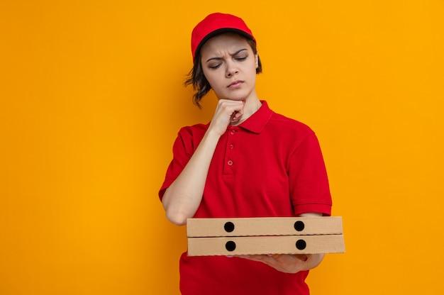 Clueless jonge mooie bezorger die pizzadozen vasthoudt en bekijkt en hand op haar kin legt