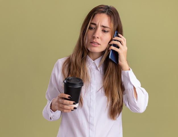 Clueless jonge, mooie blanke meid houdt een papieren beker vast en praat over de telefoon