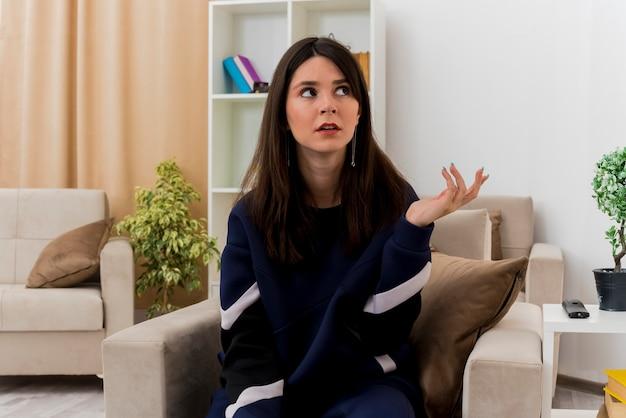 Clueless jonge mooie blanke vrouw zittend op een stoel in ontworpen woonkamer met lege hand en kant kijken