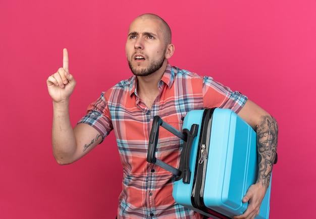 Clueless jonge reiziger man die koffer vasthoudt en omhoog wijst geïsoleerd op roze muur met kopieerruimte