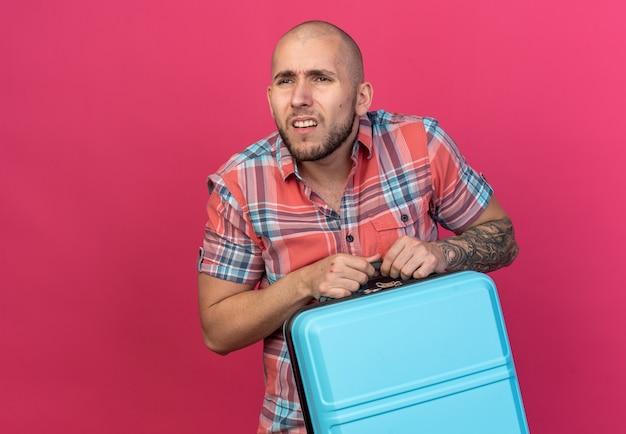 Clueless jonge reiziger man met koffer en kijken naar kant geïsoleerd op roze muur met kopie ruimte