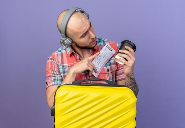 Clueless jonge reiziger man op koptelefoon met vliegticket en kijken naar papieren beker staande achter koffer geïsoleerd op paarse muur met kopie ruimte