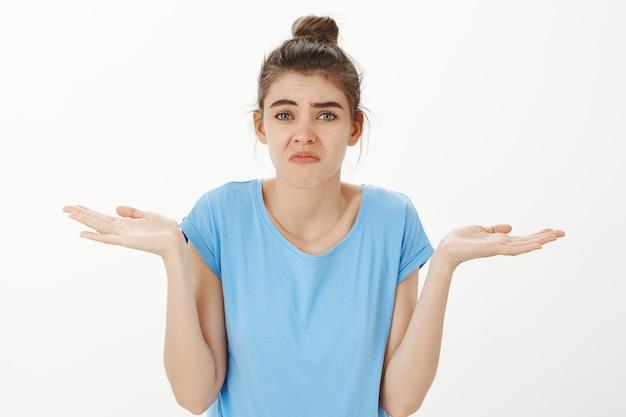 Clueless jonge vrouw schouderophalend en grimassen onbewust, weet niets