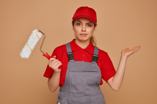 Clueless jonge vrouwelijke bouwvakker die glb en de eenvormige rol van de holdingsverf draagt die lege hand toont