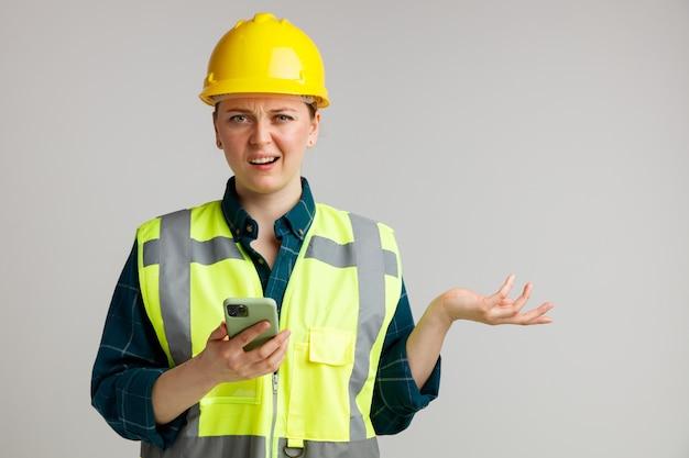 Clueless jonge vrouwelijke bouwvakker die veiligheidshelm en veiligheidsvest draagt die mobiele telefoon houdt die lege hand toont