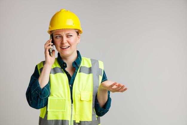 Clueless jonge vrouwelijke bouwvakker die veiligheidshelm en veiligheidsvest draagt ?? die op telefoon spreekt die kant bekijkt die lege hand toont