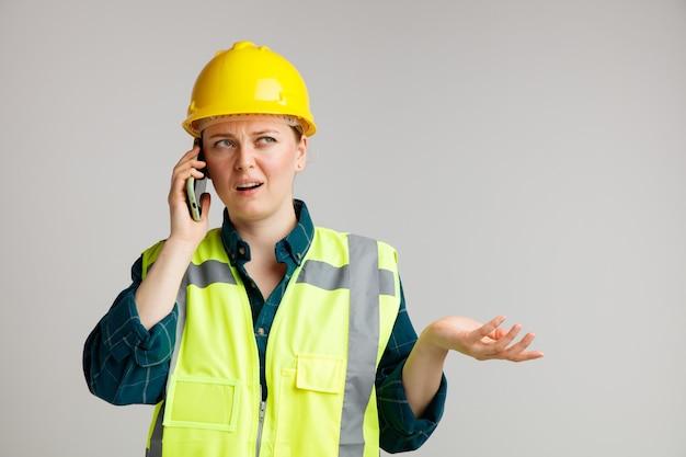 Clueless jonge vrouwelijke bouwvakker die veiligheidshelm en veiligheidsvest draagt ?? die op telefoon spreekt die omhoog bij hoek kijkt die lege hand toont