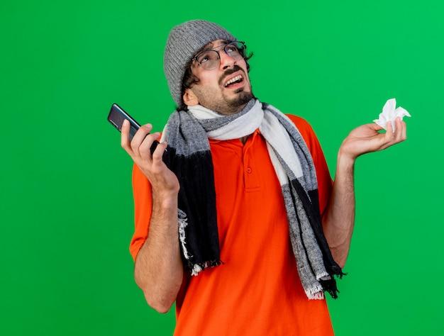 Clueless jonge zieke man met bril, muts en sjaal met mobiele telefoon en servet opzoeken geïsoleerd op groene muur