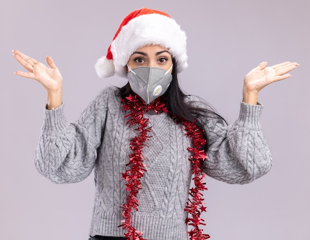 Clueless kaukasisch meisje met kerstmuts en klatergoud slinger rond nek met beschermend masker kijken camera weergegeven: lege handen geïsoleerd op witte achtergrond