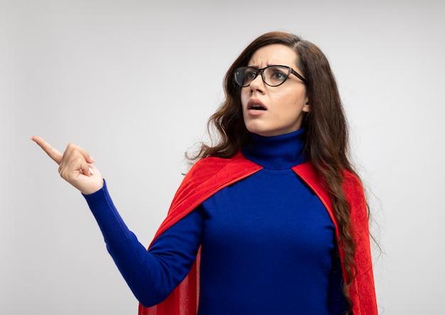 Clueless kaukasisch superheld meisje met rode cape in optische bril kijkt en wijst naar de zijkant op wit