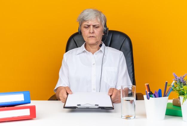 Clueless kaukasische vrouwelijke callcenter-operator op koptelefoon zittend aan een bureau met kantoorhulpmiddelen vasthouden en kijken naar klembord