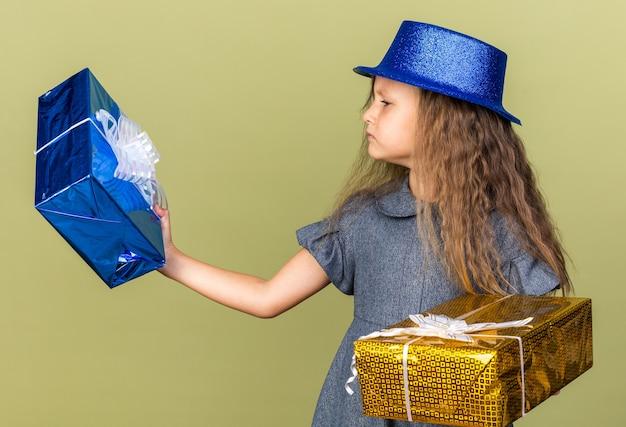 Clueless klein blond meisje met blauwe feestmuts houden en kijken naar geschenkdozen geïsoleerd op olijfgroene muur met kopie ruimte