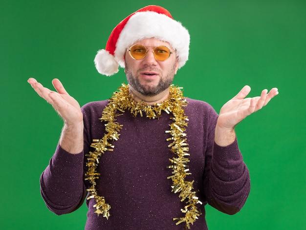 Clueless man van middelbare leeftijd met kerstmuts en klatergoud slinger rond nek met bril kijken camera weergegeven: lege handen geïsoleerd op groene achtergrond