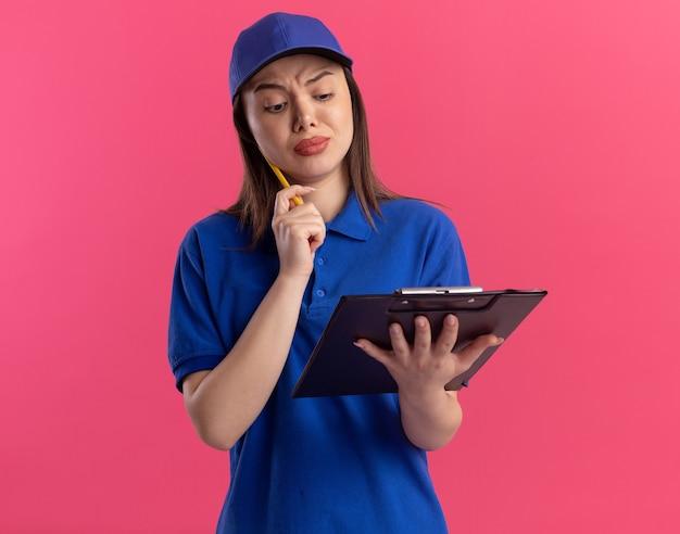 Clueless mooie bezorger in uniform zet potlood op kin en kijkt naar klembord