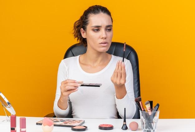 Clueless mooie blanke vrouw zittend aan tafel met make-up tools houden oogschaduw palet en kijken naar make-up borstel geïsoleerd op oranje muur met kopie ruimte