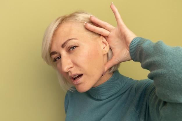 Clueless mooie blonde slavische vrouw houdt hand achter oor geïsoleerd op olijfgroene muur