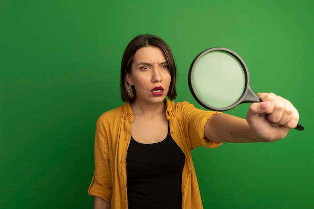 Clueless mooie vrouw houdt en kijkt naar vergrootglas geïsoleerd op groene muur