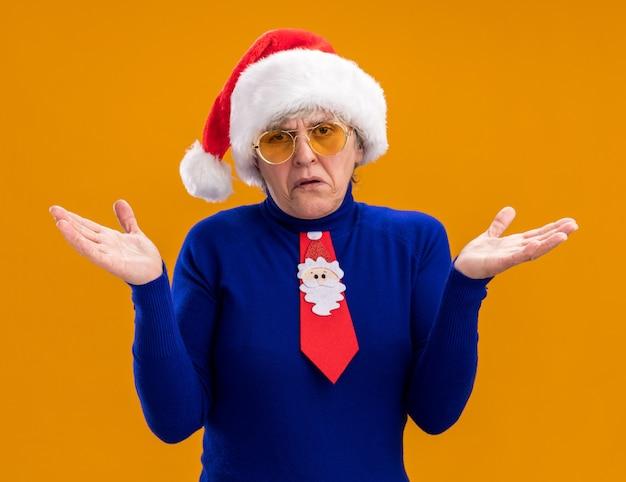 Clueless oudere vrouw in zonnebril met kerstmuts en kerst stropdas hand in hand open geïsoleerd op een oranje achtergrond met kopie ruimte